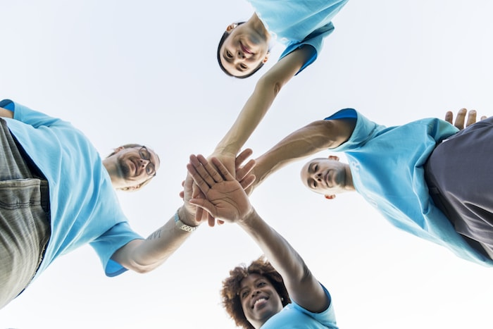 Group of happy and diverse volunteers stacking their hands on top of each other