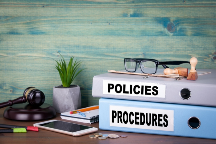 Policies and procedures binders stacked on desk