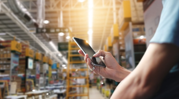Man's hand using smartphone in large warehouse
