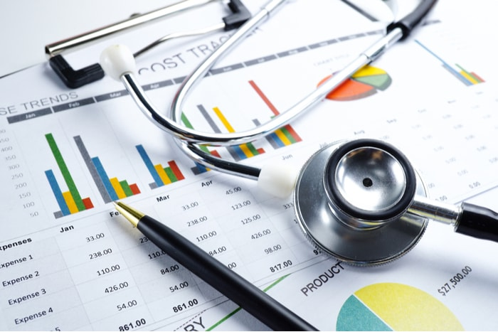 Stethoscope and pen lying on top of financial charts and graphs